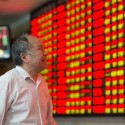 Investor observes stock market at a stock exchange hall
