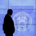 A security guard walks in front of an image of the Federal Reserve in Washington, DC, U.S.